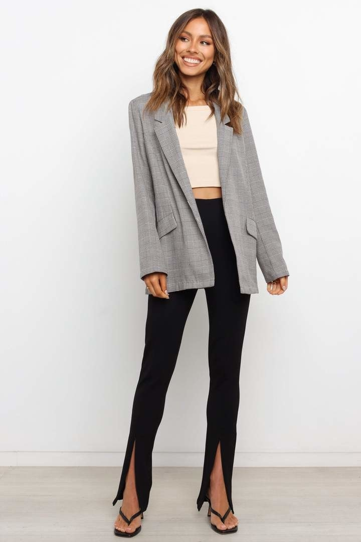 model wearing a tweed longline blazer over a crop top and black pants