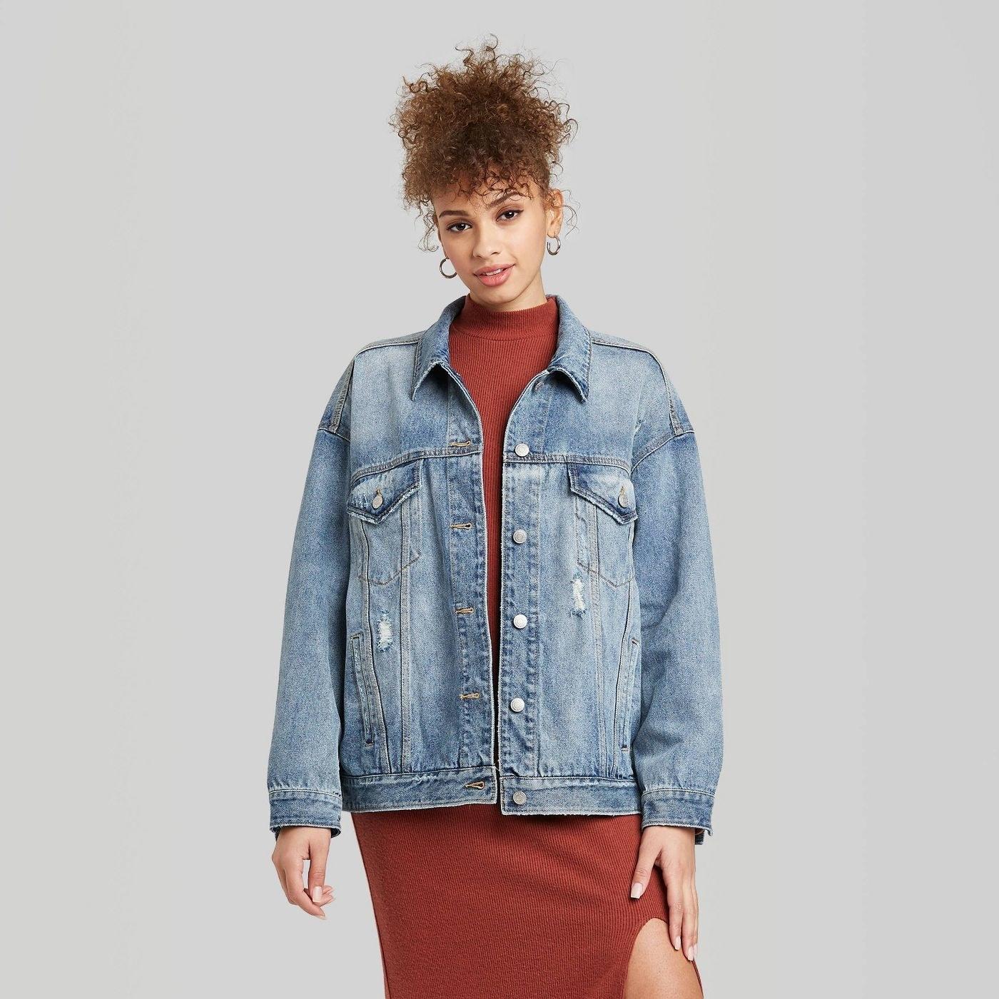 model wearing a blue oversized jean jacket over a dress