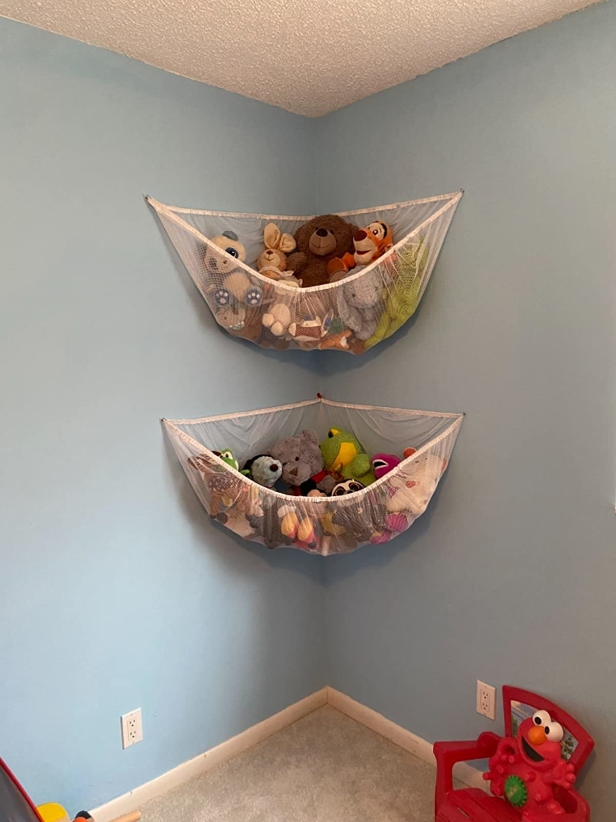 Reviewer's photo showing a pair of white hammocks holding stuffed animals and hanging on a blue wall