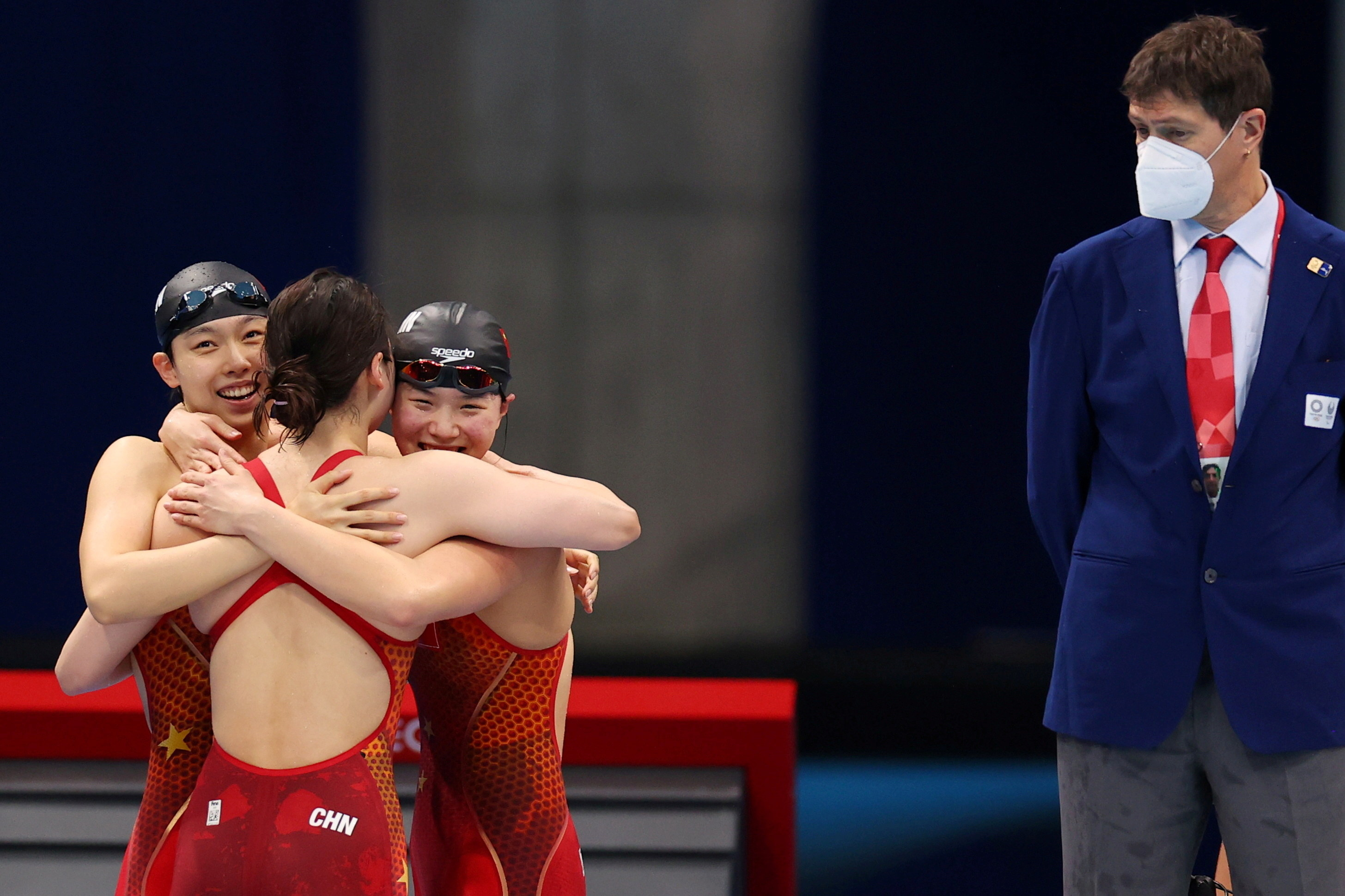 Olympic swimmers share a hug after winning a gold medal at the Olympics