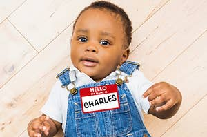 """A cute baby wearing overalls and a name tag that says, """"Hello, My name is Charles"""""""