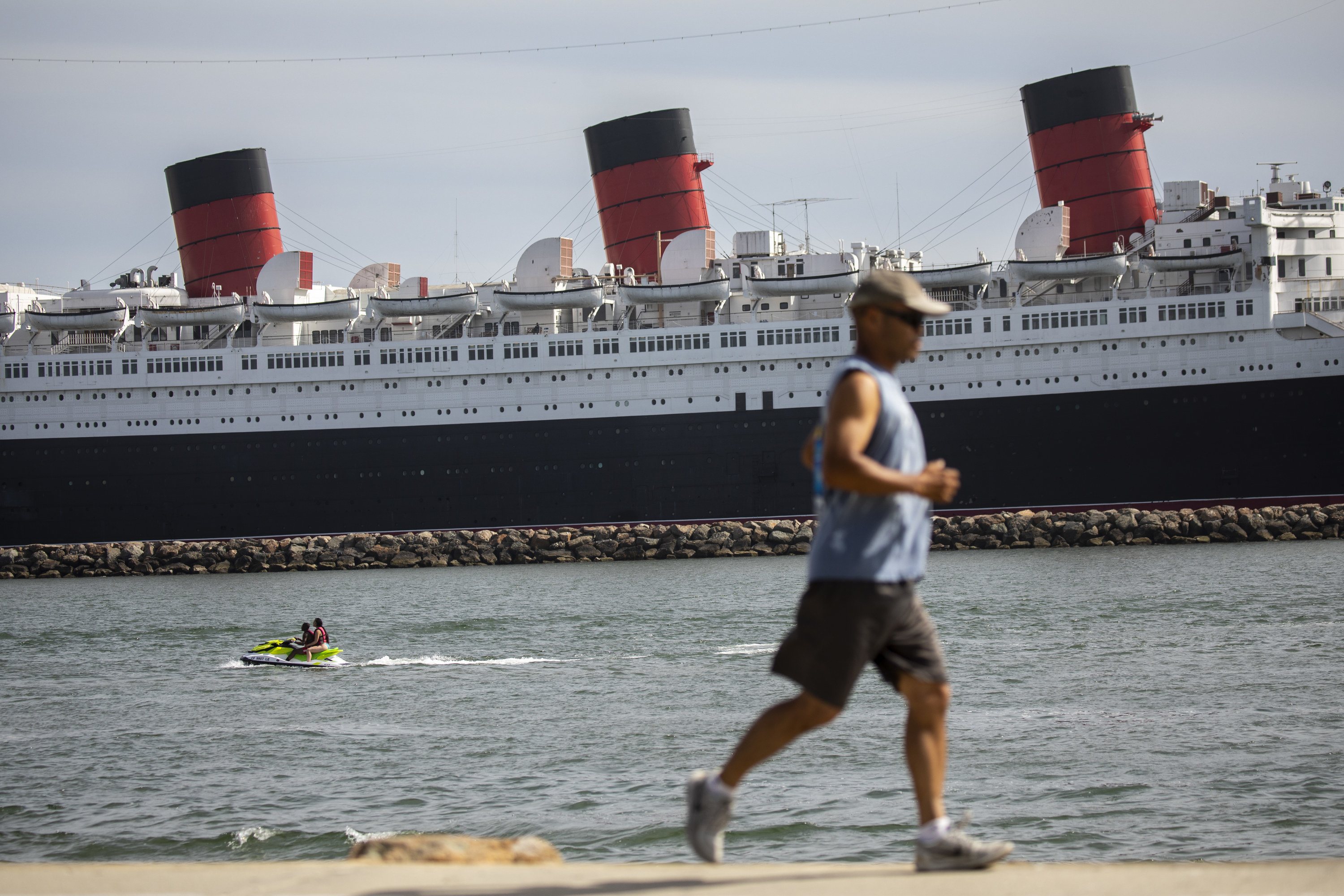 Two people on a jetski are seen in the water, while a runner passes by along Shoreline Aquatic Park, with the Queen Mary ship in the distance, docked in Long Beach, CA,