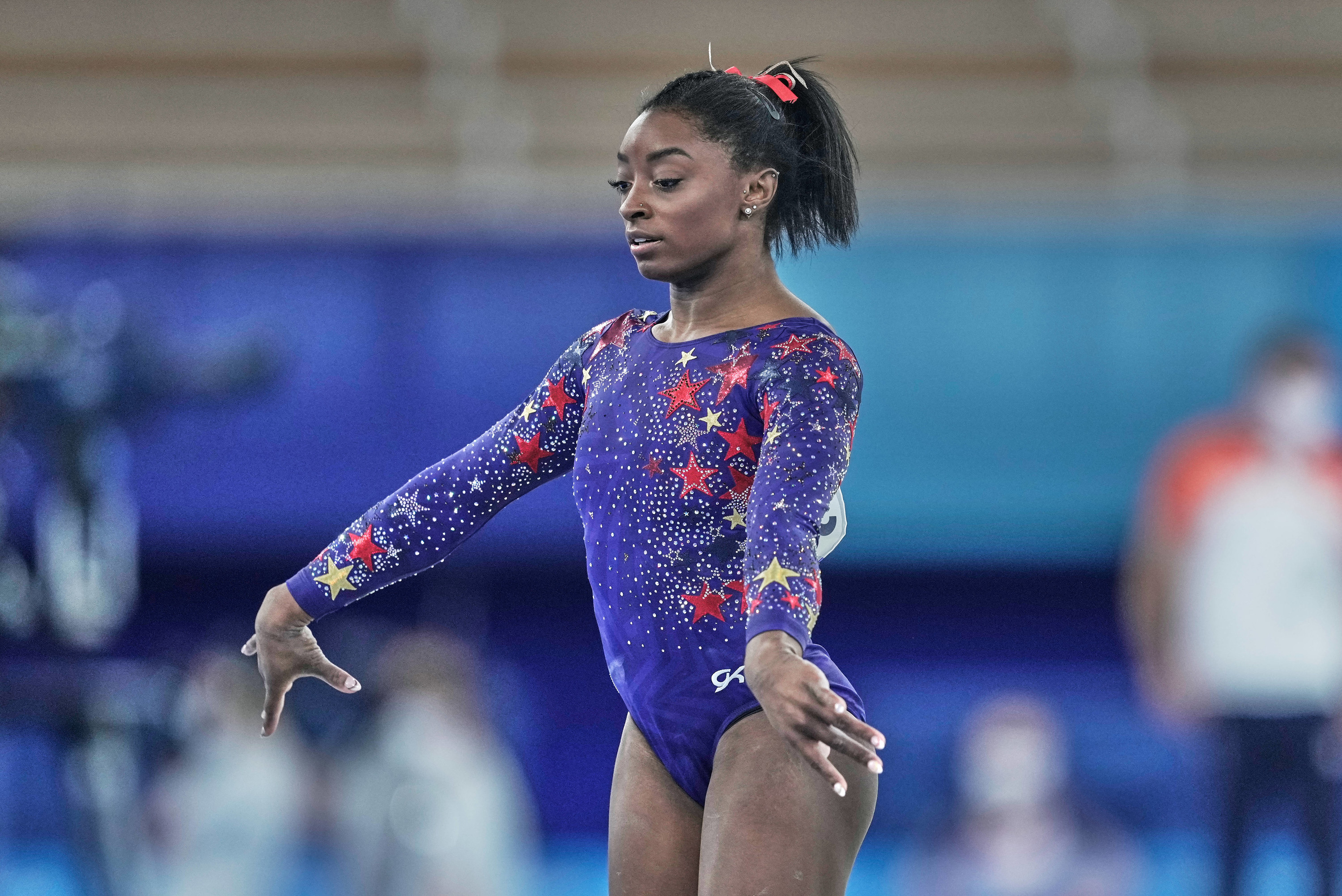 Simone Biles stands with her arms out near her sides during the artistic gymnastics final at the 2020 Olympics