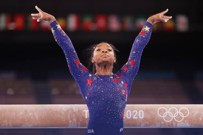 Simone poses with her arms stretched above her head after performing on the balance beam