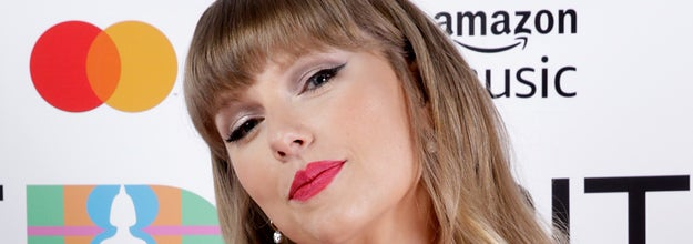 Taylor Swift poses with her hand on her hip at a red carpet event while wearing a two-piece outfit