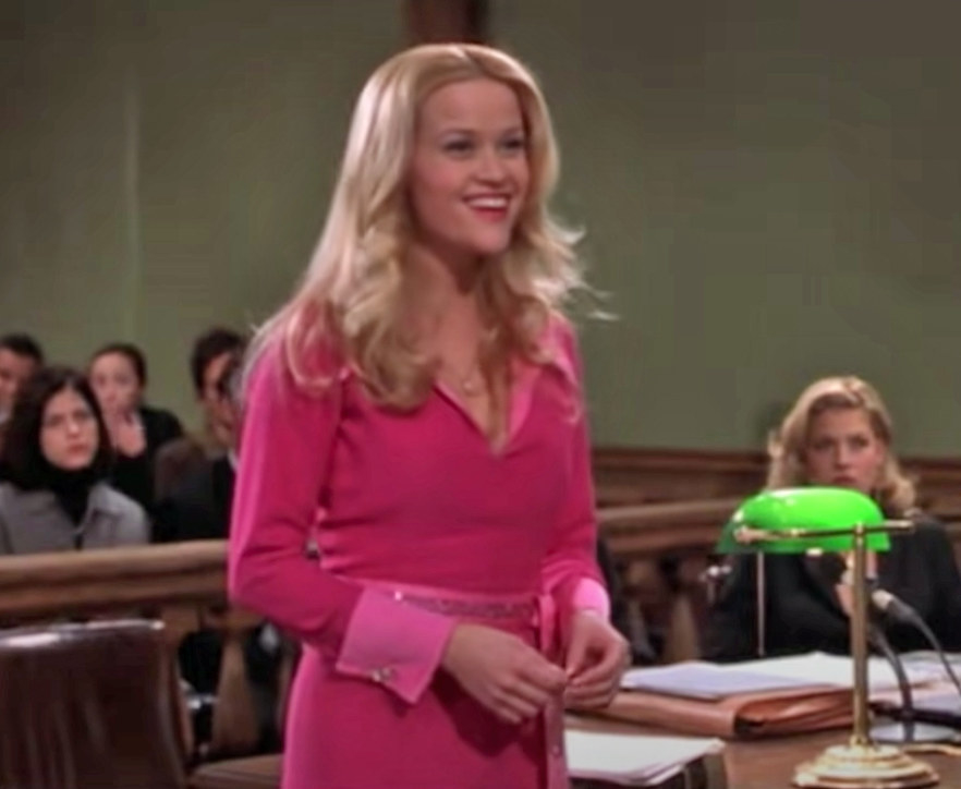 Elle Woods stands up in the courtroom and smiles brightly while wearing a coordinated and stylish outfit