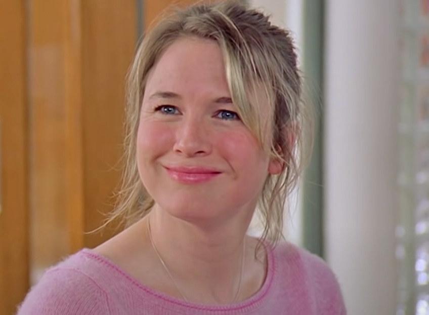Renée Zellweger smiles a tight-lipped smile in the office as Bridget Jones