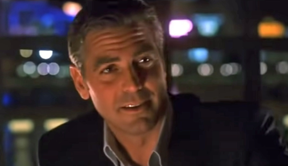 George Clooney sits in a bar at night and smiles as Danny