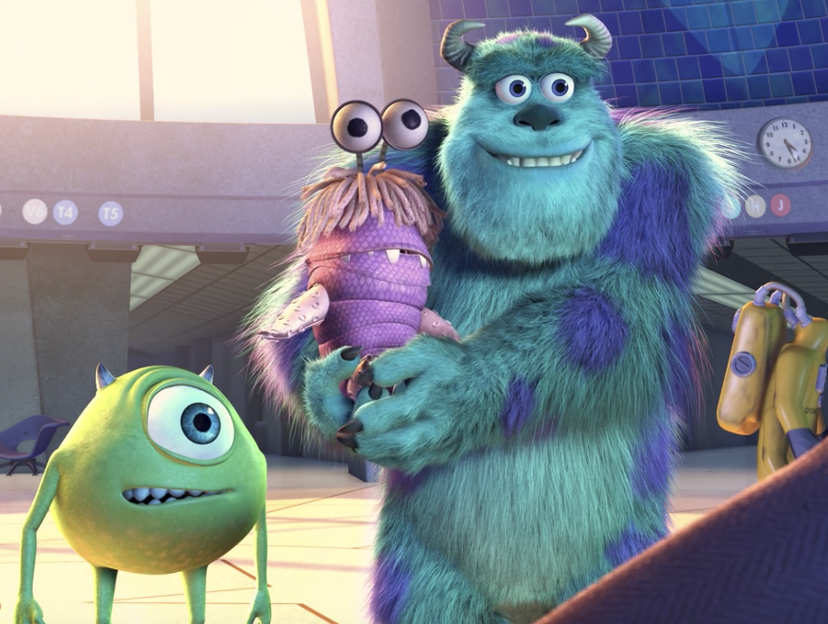 Mike smiles a crooked smile while Sulley smiles an equally awkward smile as he holds Boo in a monster suit