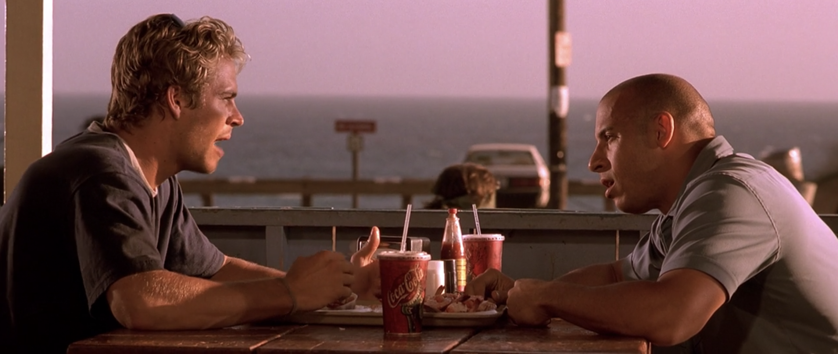 Paul Walker and VinDiesel sit across from each other at a table with a tray of food and drinks in front of them as Brian and Dom