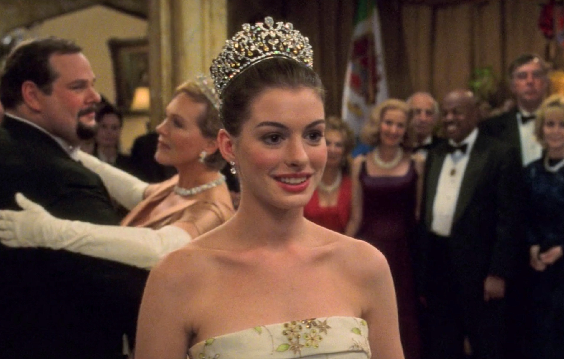 Mia stands in the middle of the room wearing a crown and gown and soft smile