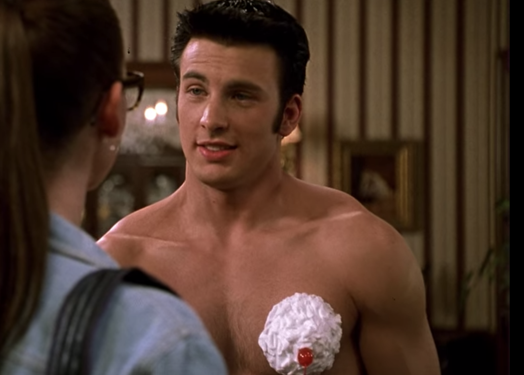 Chris Evans smiles a crooked smile with whipped cream and cherries covering his nipples asJake