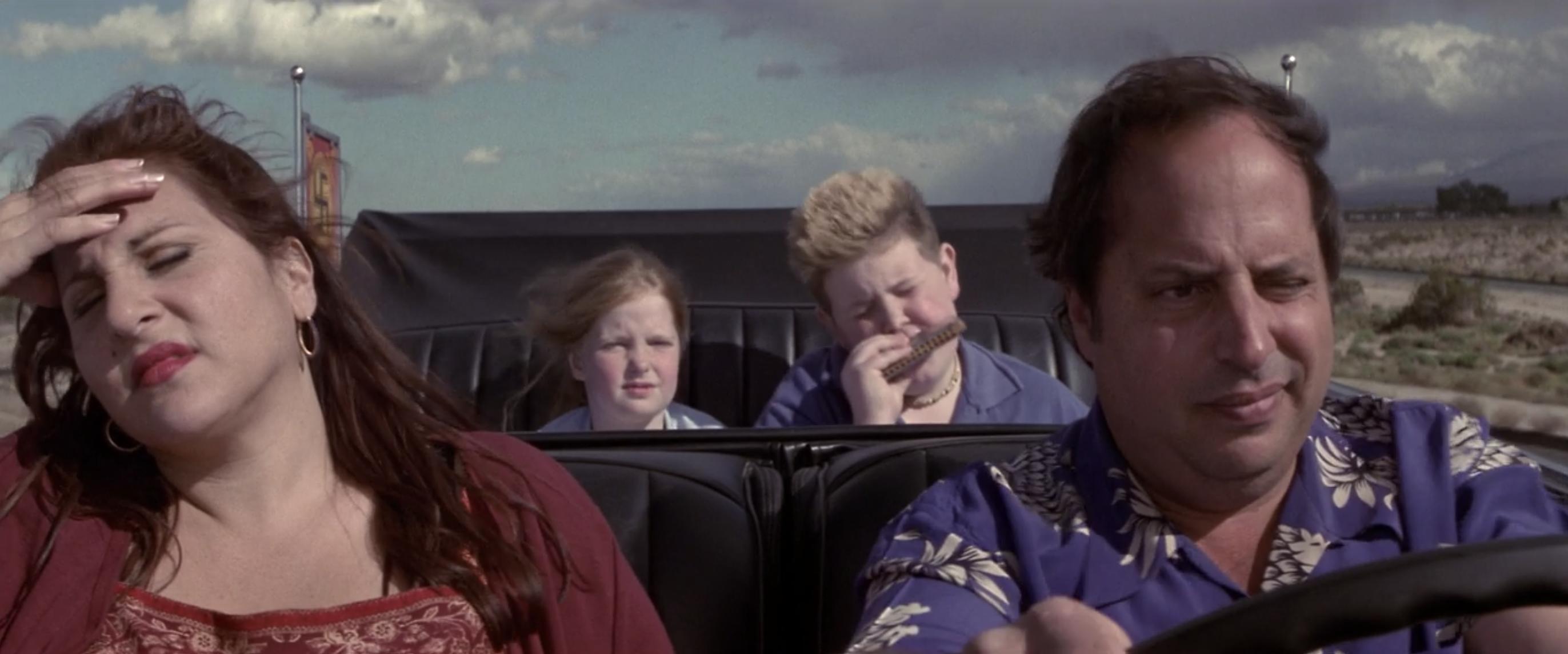 Kathy Najimy, Jon Lovitz, Jillian Marie Hubert, and Brody Smith sit in a convertible driving down a deserted road as Bev, Randy, Kimberly, and Jason