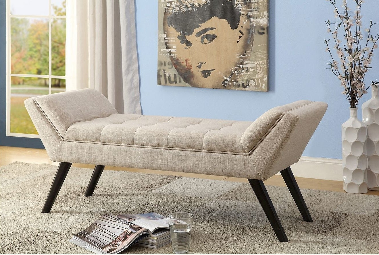 an upholstered bench with winged arms on four wooden legs