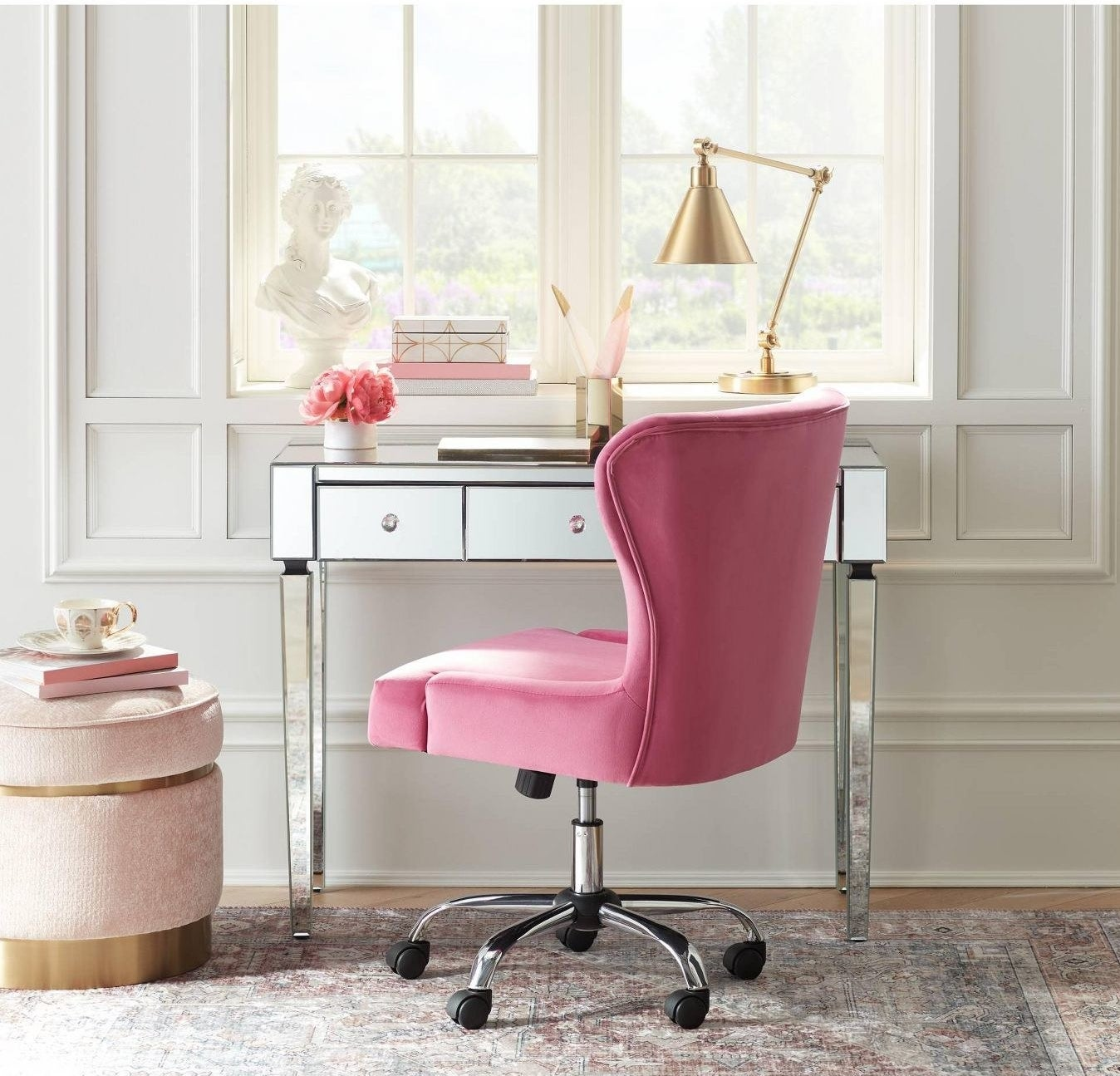 a mirrored desk with a bright pink desk chair