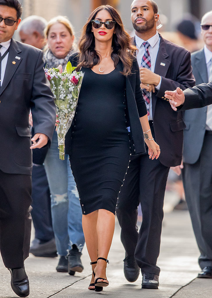 A pregnant Megan walking along the street in a crowd and holding flowers