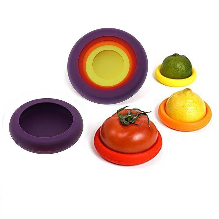 Purple, red, orange and yellow silicone food savers with a halved tomato and a halved lemon