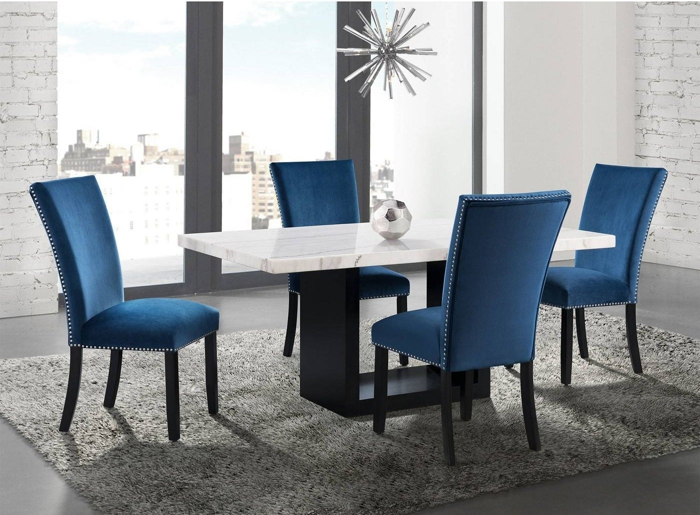 a marble dining table with a black base surrounded by teal velvet dining chairs