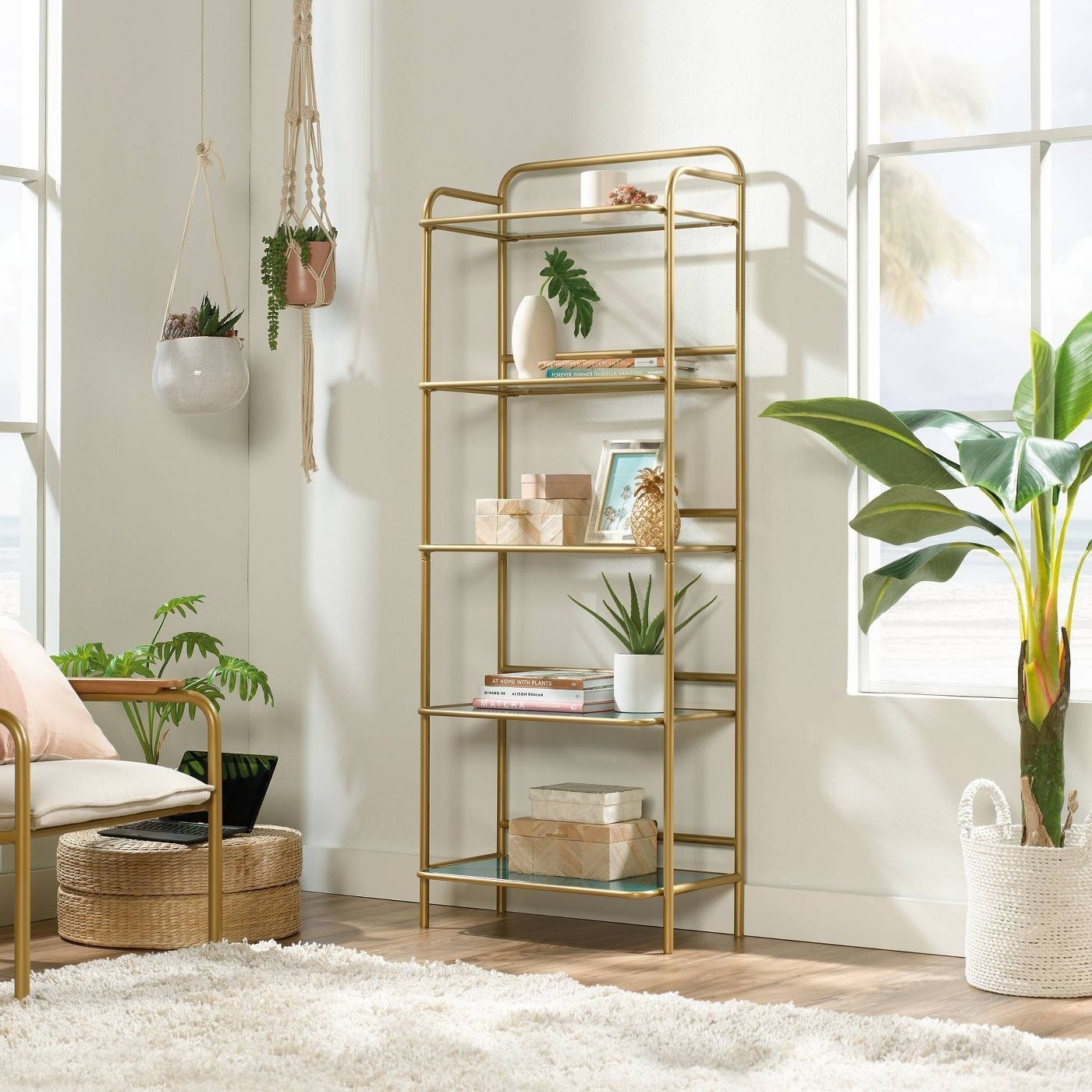 a gold book shelf with glass and teal-tinted shelves