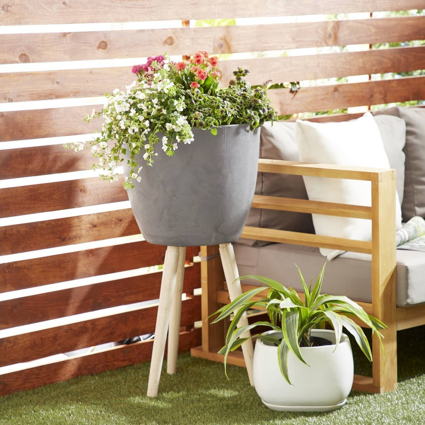 a clay planter on four wooden legs