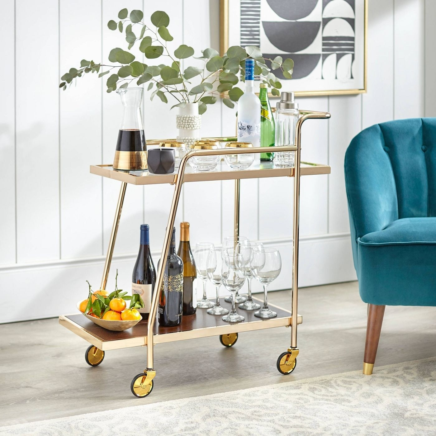 a gold rolling bar cart filled with glasses and bottles of alcohol