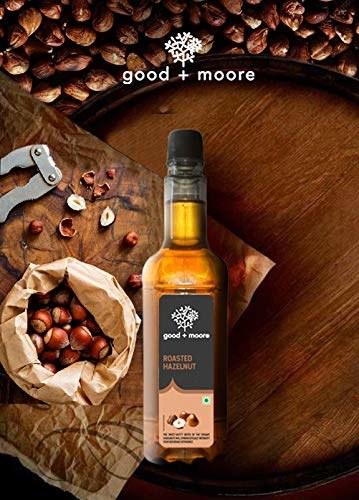 A bottle of roasted hazelnut coffee syrup beside some hazelnuts in a bag