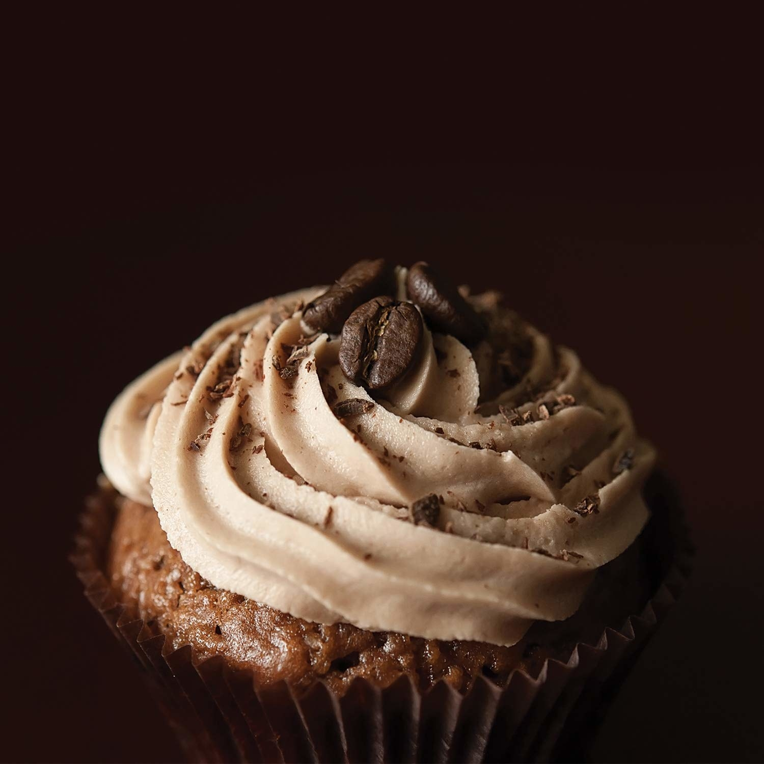 A cupcake with icing on it and two coffee beans on top.