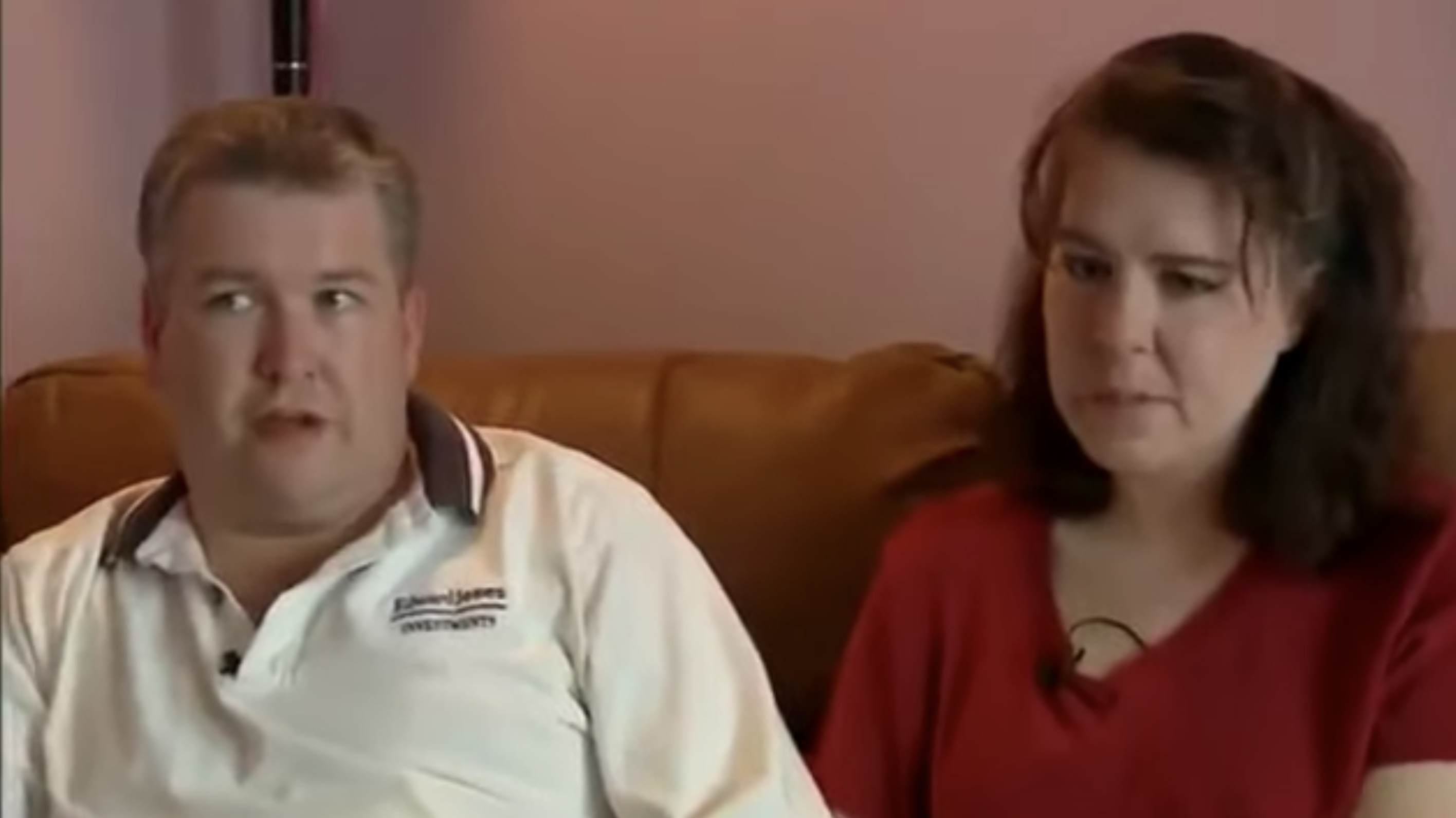 Couple sitting on their couch looking upset