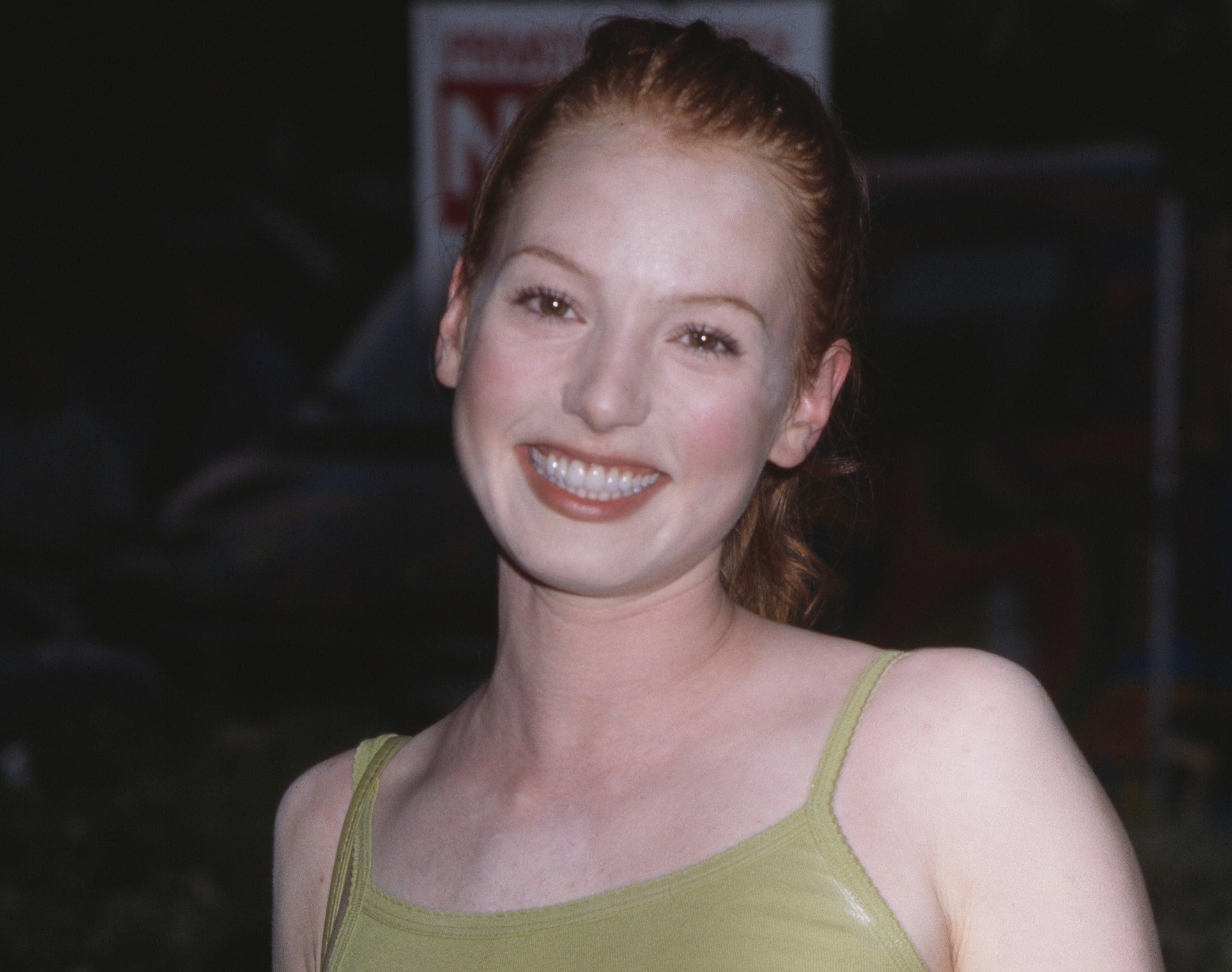 A young Alicia smiles while wearing a green tank top