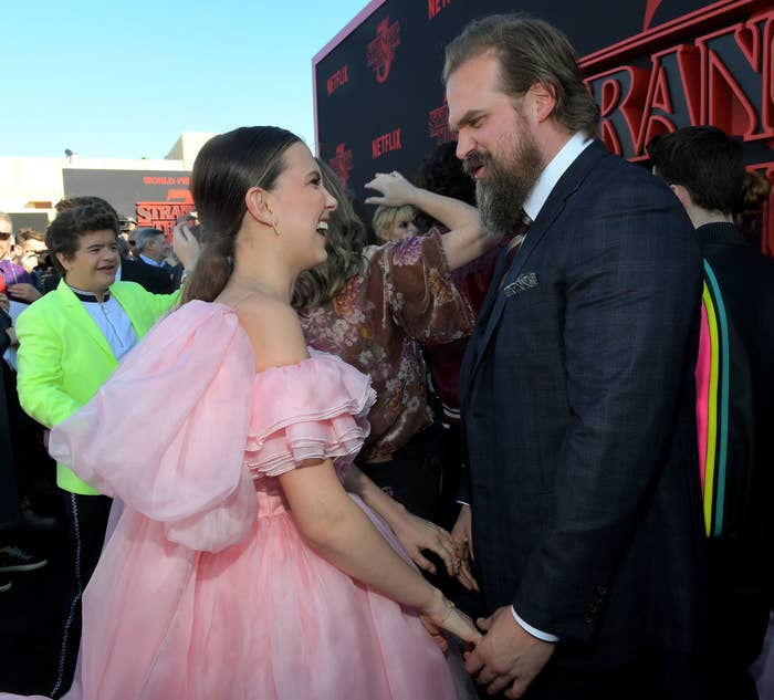 """Millie Bobby Brown (L) and David Harbour holding hands and smiling at each other at the """"Stranger Things"""" Season 3 World Premiere"""