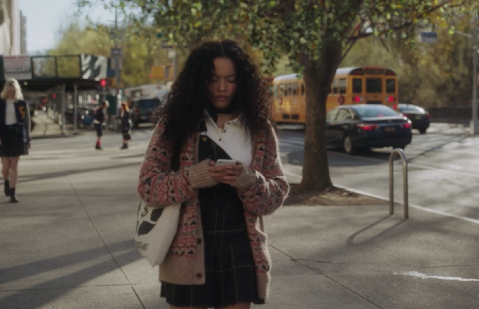 Zoya wears a plaid uniform jumper skirt with one strap attached to the top button, over a T-shirt with a patterned cardigan on top