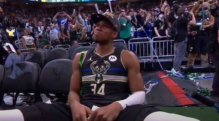 Emotional Giannis Antetokounmpo sits in a chair while wearing a champions hat