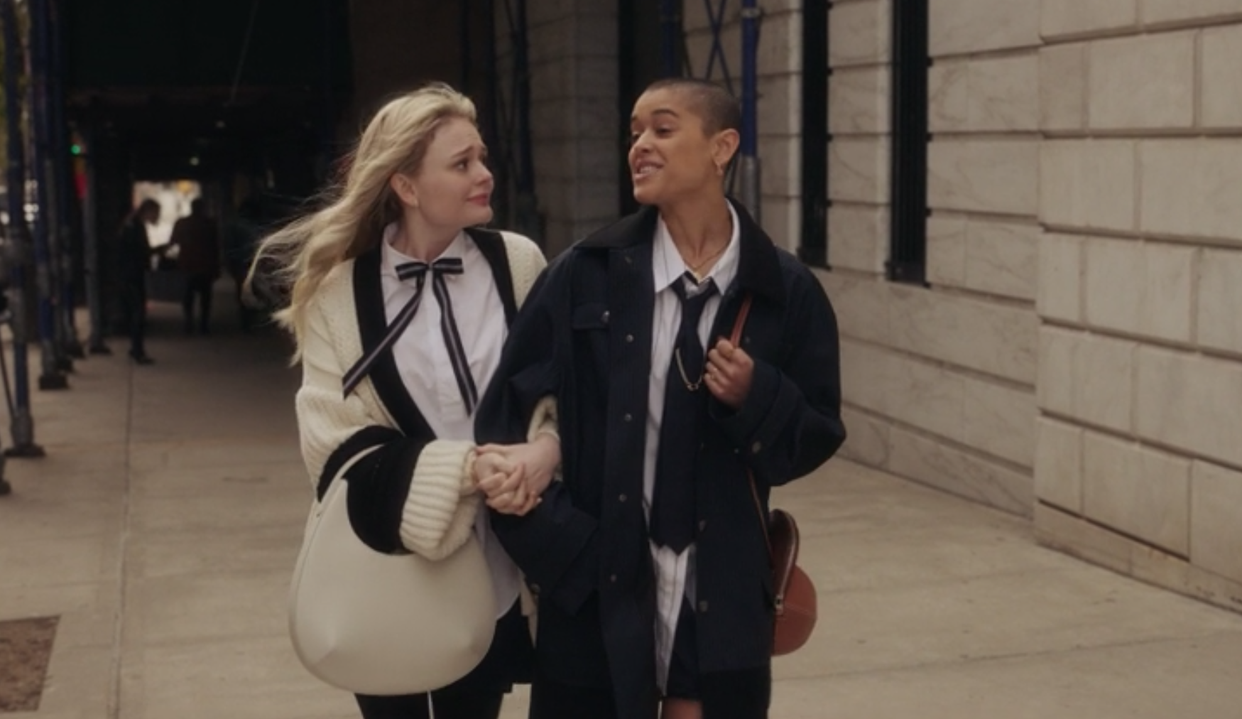 Audrey wears an oversize knit sweater with a skinny bow tie, and Julien wears a pin-striped button-up shirt, dark tie, and matching oversize jacket