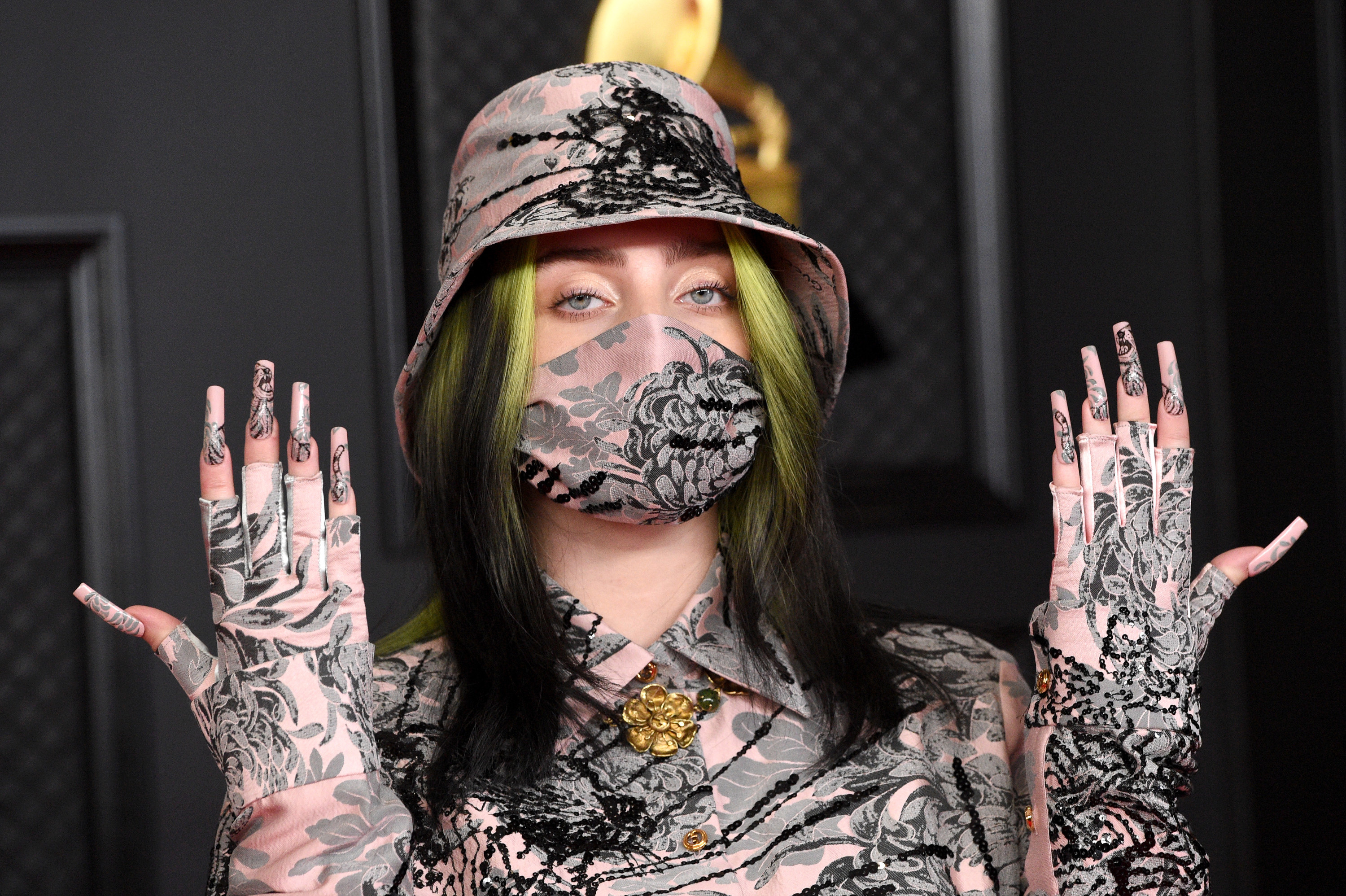 Billie showing off her floral printed nails that match her top, bucket hat, and face mask at the Grammys
