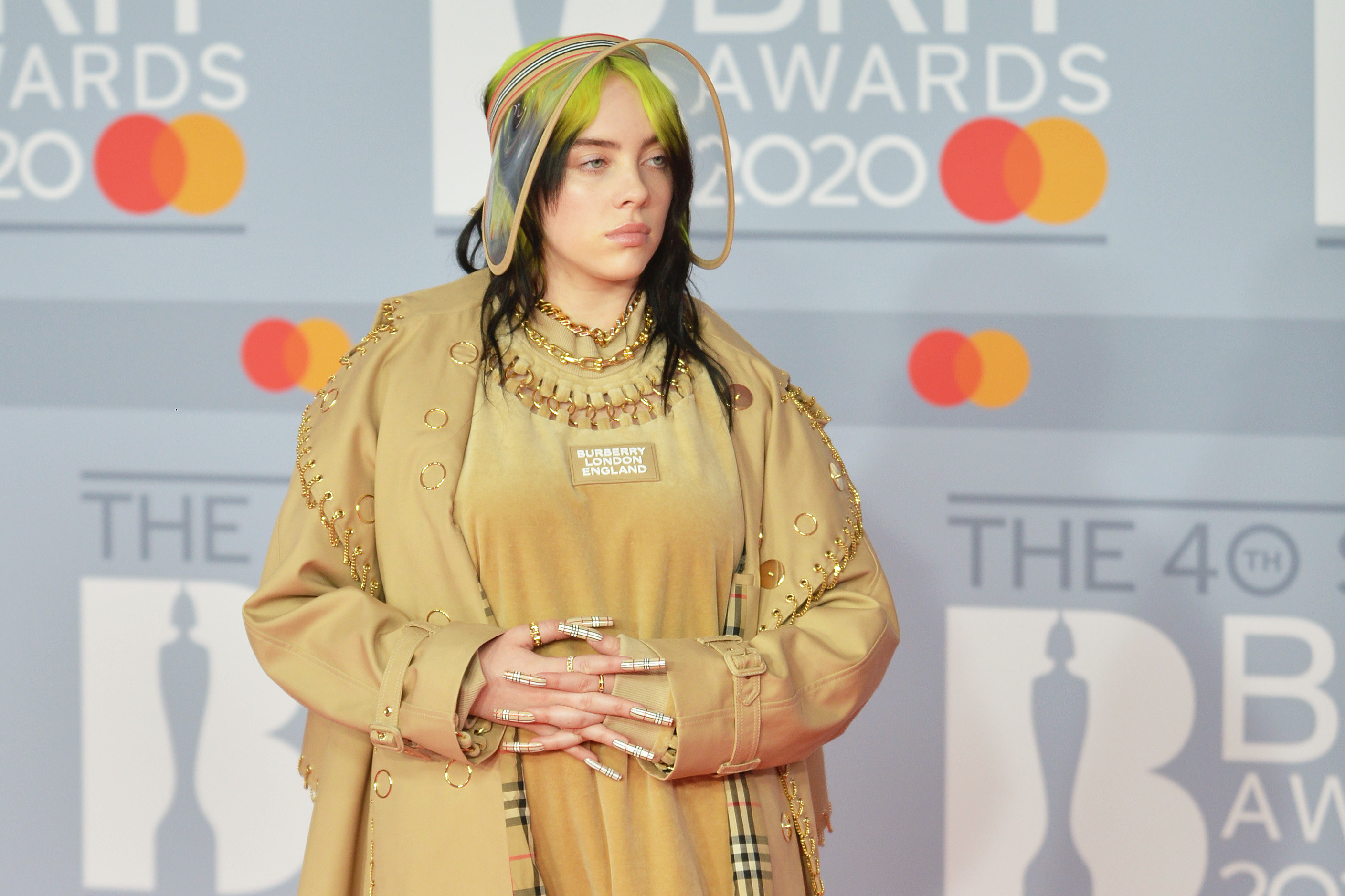 Billie on the red carpet of the 2020 Brit Awards wearing a light-colored jacket and top and an oversize visor