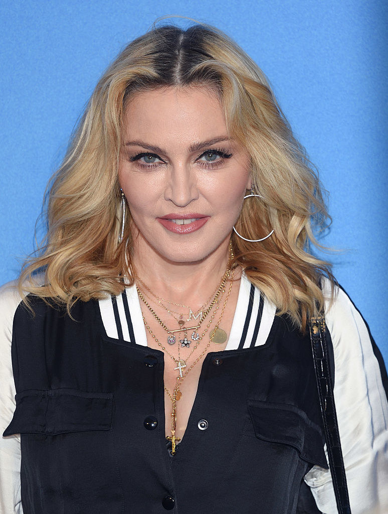 Madonna, wearing large hoop earrings and many necklaces, including a cross and the letter M, smiles for the camera