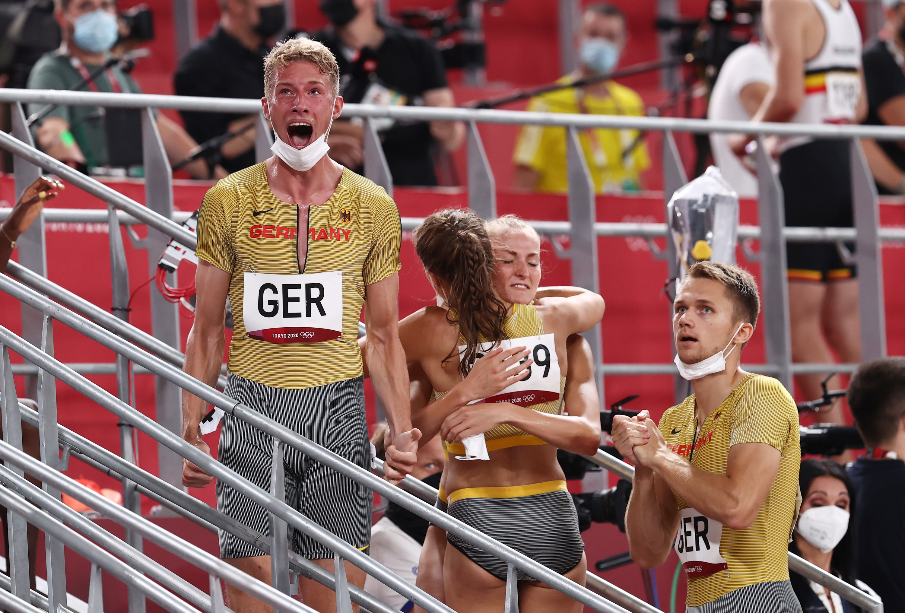 Four athletes standing on stairs scream in celebration, hug, and react with surprise to the results of their event