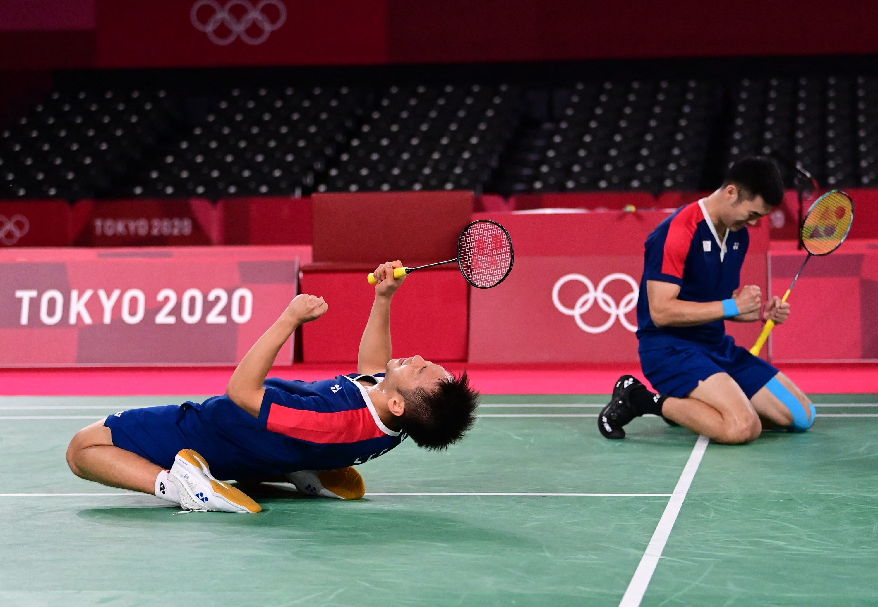 Two badminton players pump their fists and kneel on the badminton court