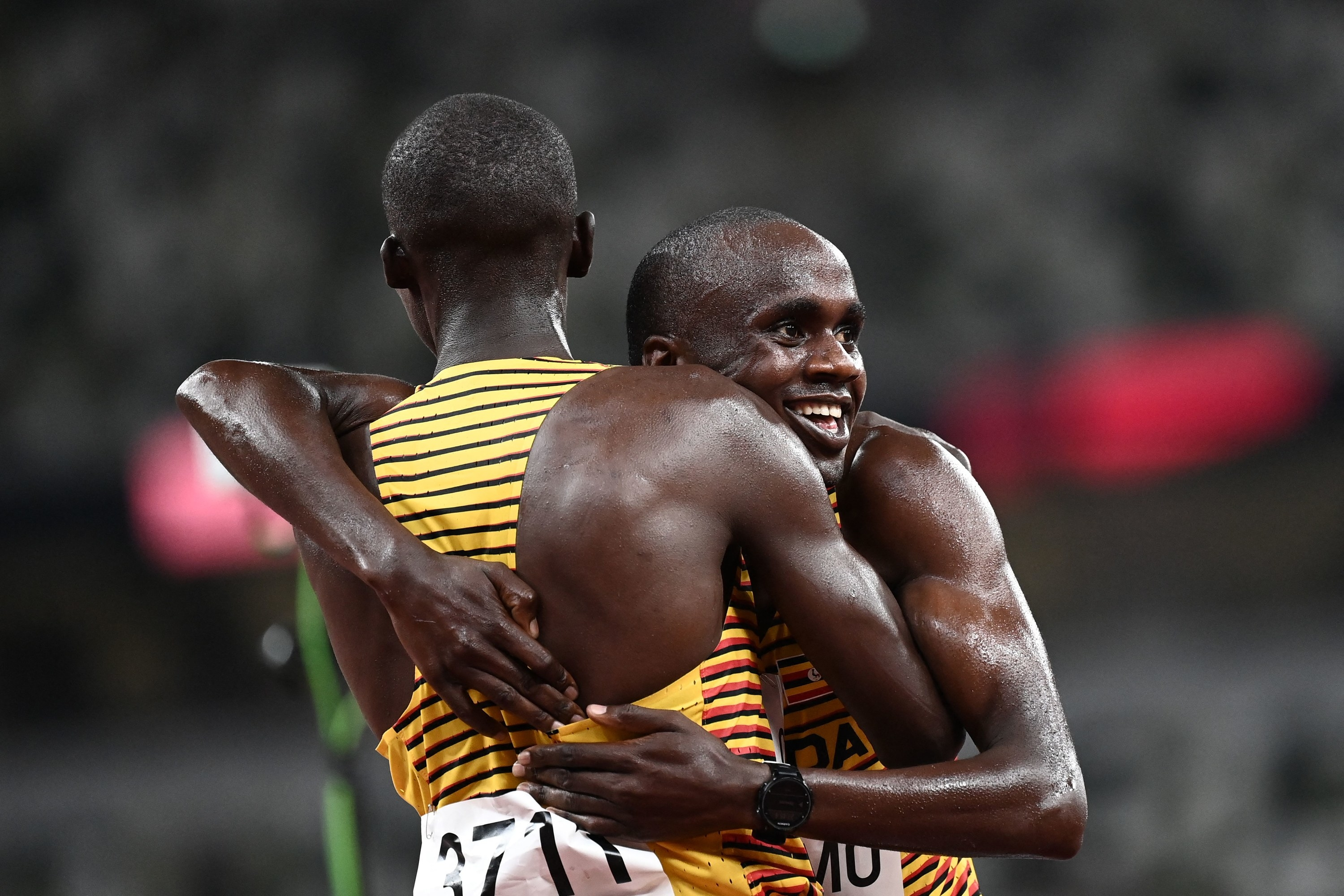 Ugandan runners embrace after competing on the track at the Olympics.