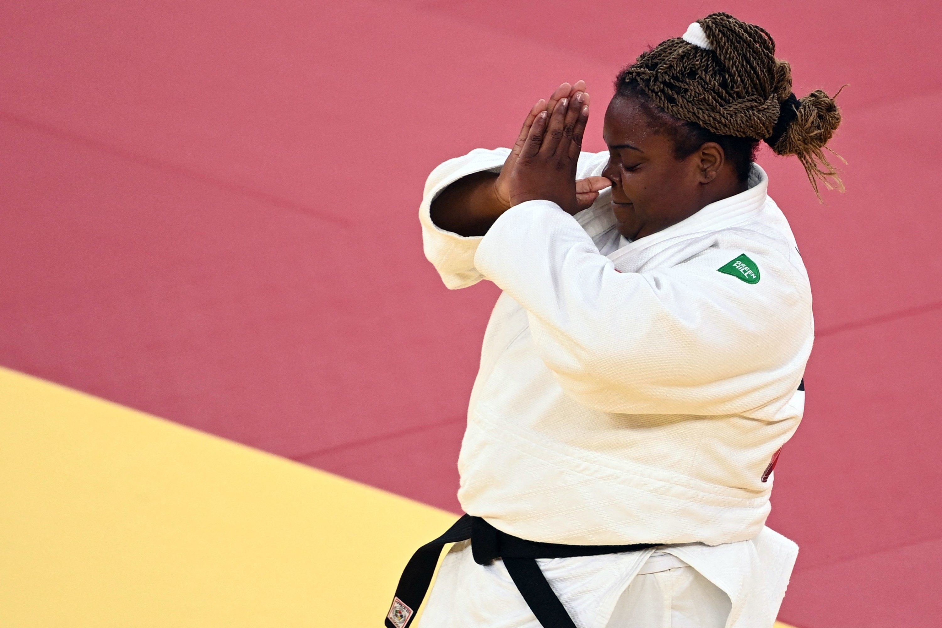 An Olympic medalist raises her hands in prayer after winning a judo competition