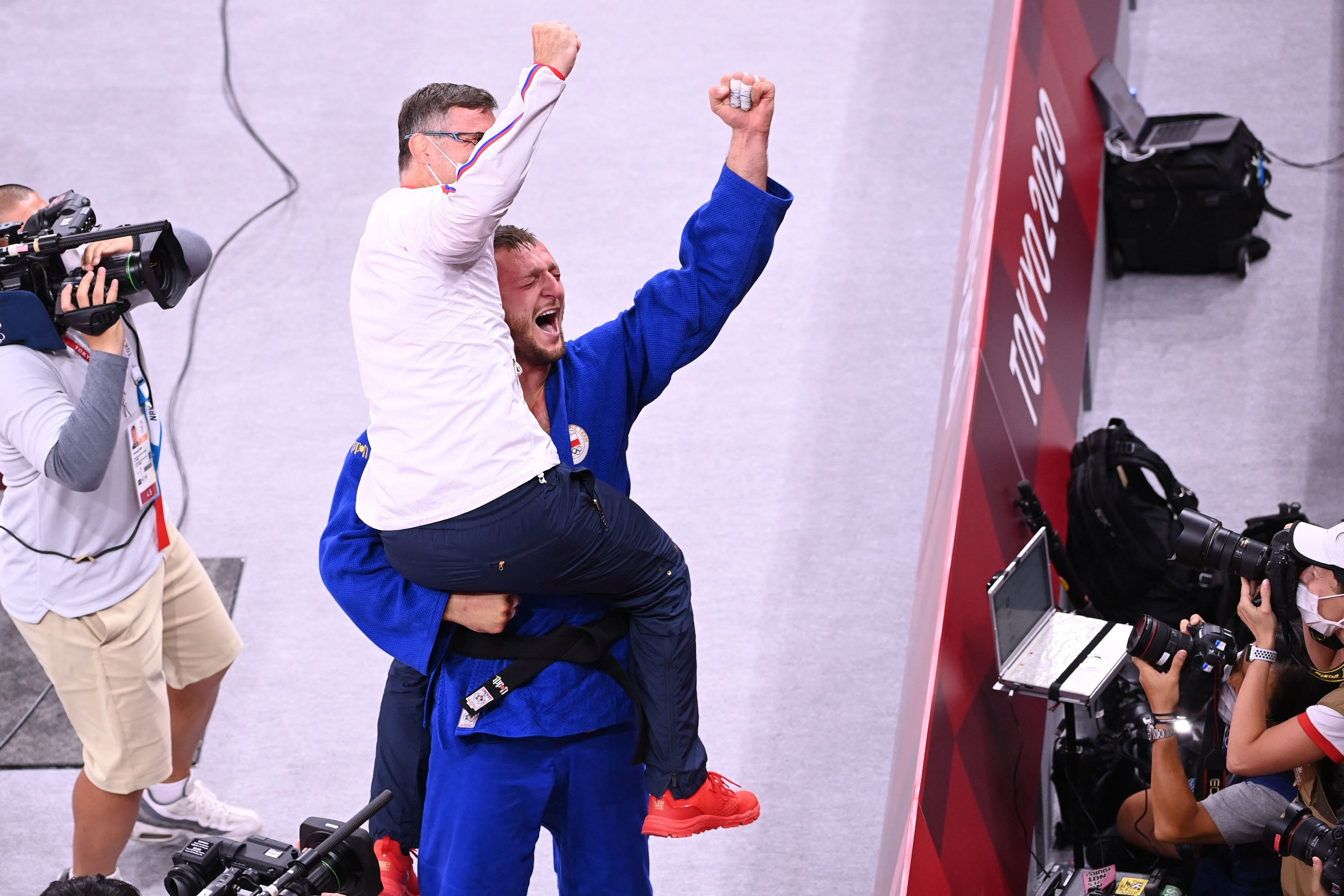 An Olympic athlete lifts up his coach after winning an event with both of them raising their fists in celebration