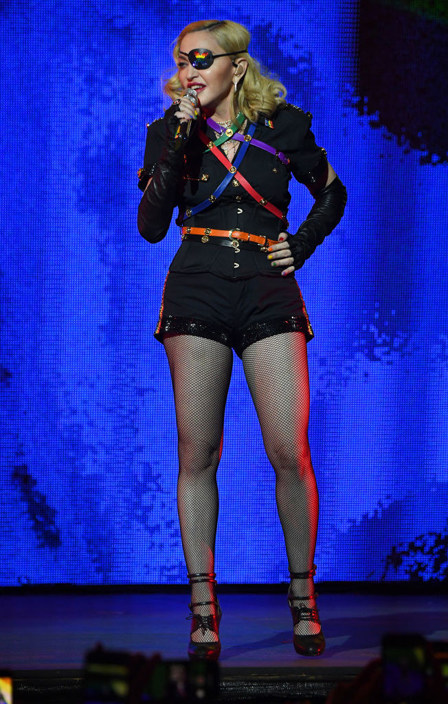 Madonna wearing an eye patch with pride colors and fishnet stockings and singing onstage