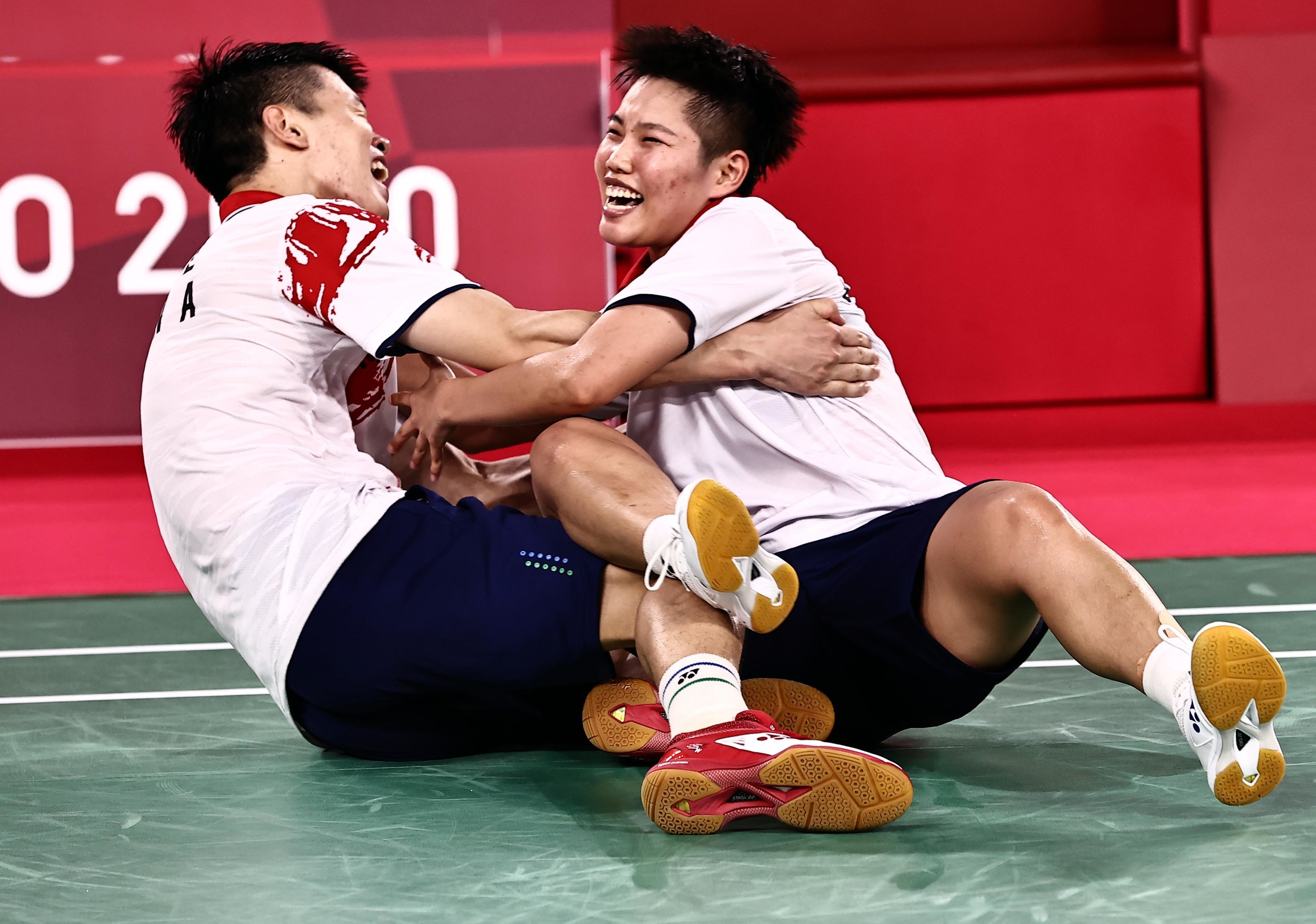 Two Olympic athletes smile and hold each other on the floor