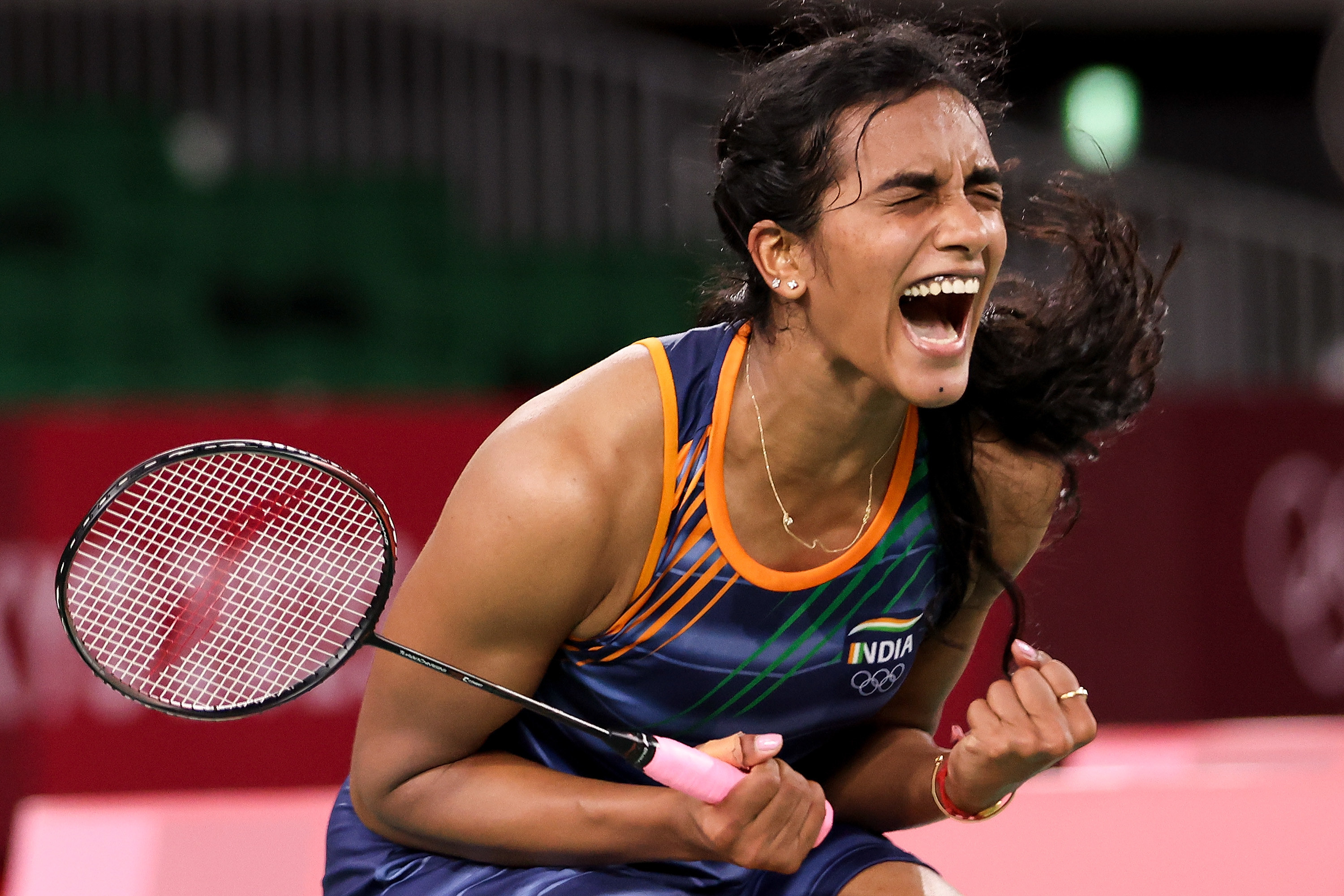 An Olympic tennis player shouts in celebration after winning a match
