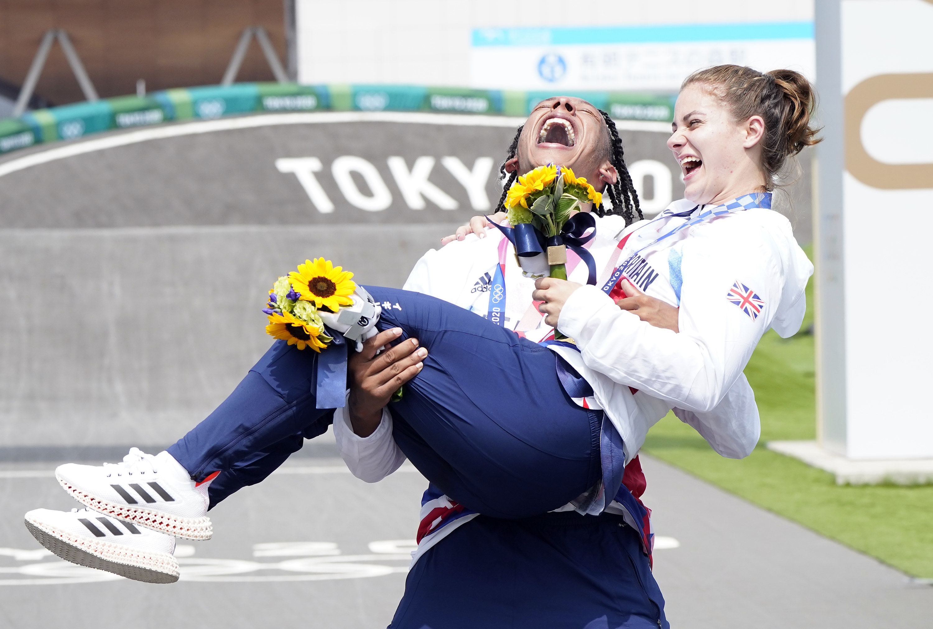 A male BMX athlete holds up a female BMX athlete in celebration of their Olympic win