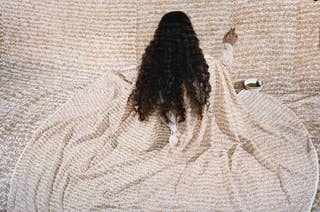 A long haired woman in a robe paints a wall with the same pattern