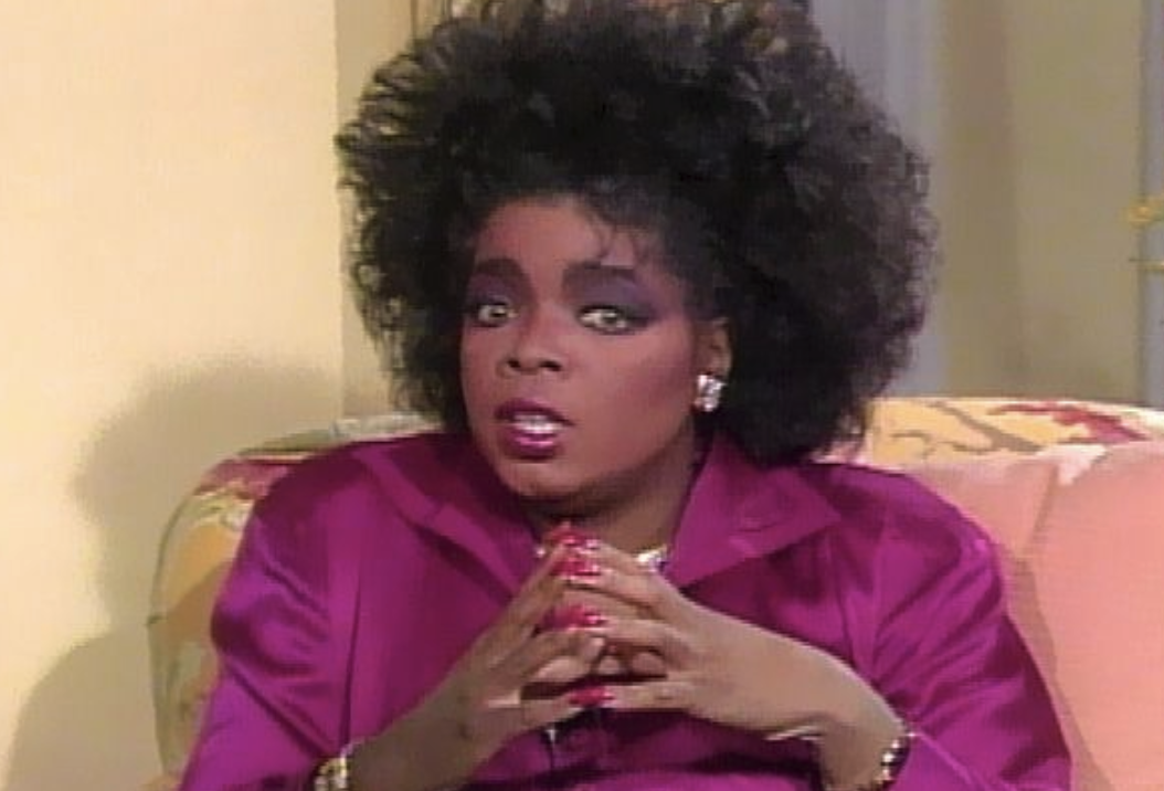 Oprah looking shocked with her fingers touching