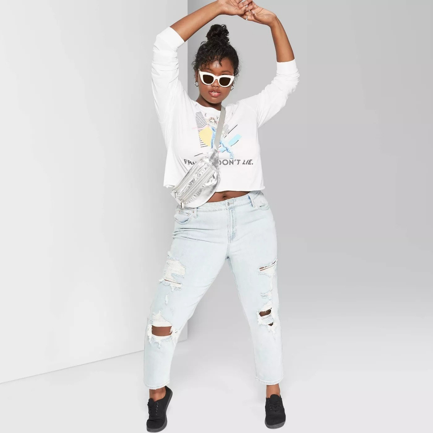 Model wearing loose fitting jeans with large holes, stops at the knee
