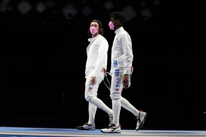 Two outfitted fencers walk side by side and wear matching face masks