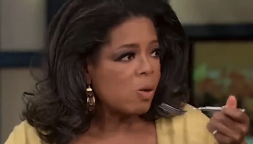 Oprah looking shocked with a fork in her hand
